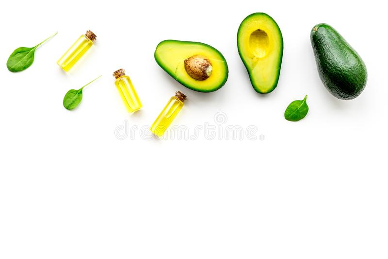 Natural products for skin care. Avocado oil in bottles near sliced avocado on white background top view copy space. Natural products for skin care. Avocado oil royalty free stock image