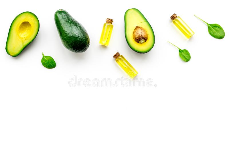 Natural products for skin care. Avocado oil in bottles near sliced avocado on white background top view copy space. Natural products for skin care. Avocado oil stock photo