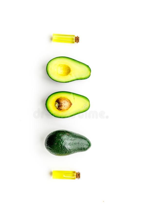 Natural products for skin care. Avocado oil in bottles near sliced avocado on white background top view copy space. Natural products for skin care. Avocado oil stock photos