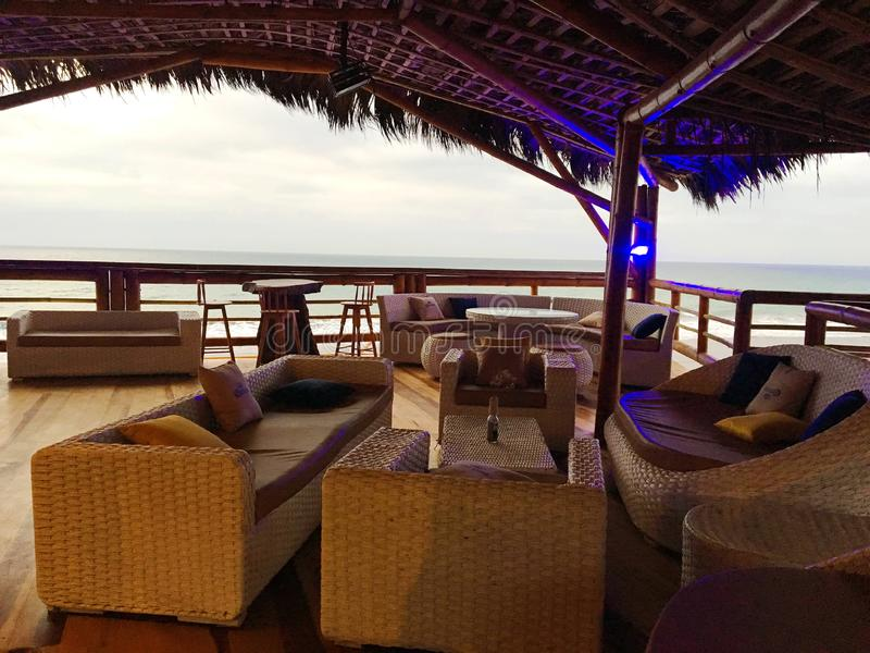 Outdoor Bar Lounge Area overlooking the Ocean. Natural rattan lounge furniture and tables in a Ecuablue, a bar built of bamboo overlooking the Pacific Ocean in royalty free stock image
