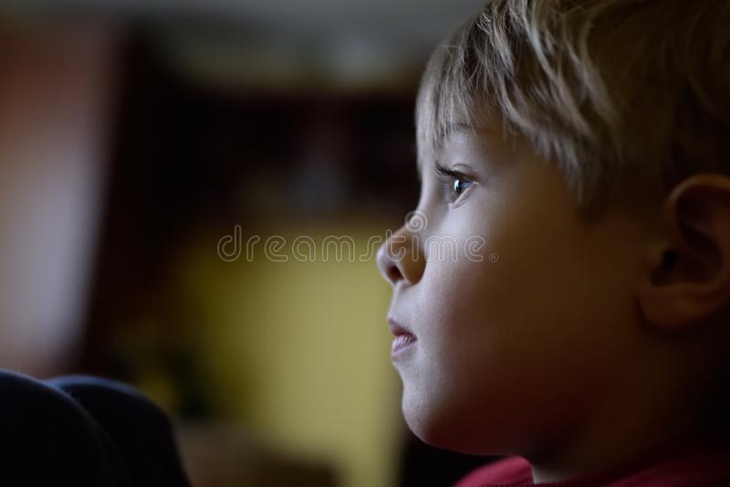 Natural, real portrait of a child, light from the window, not posed. Boy`s face, thoughtful, sad, dreamer. Longing and waiting. Profile, side view, closeup royalty free stock image