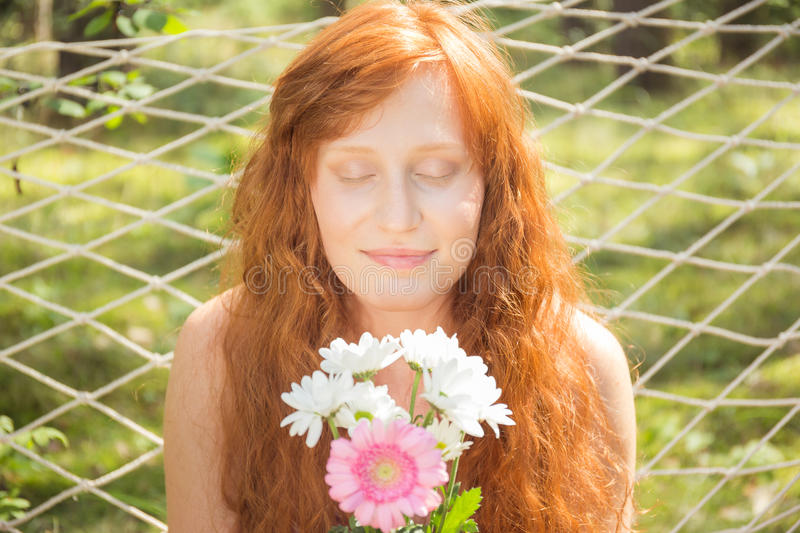 Natural red-haired woman smelling flowers royalty free stock photography