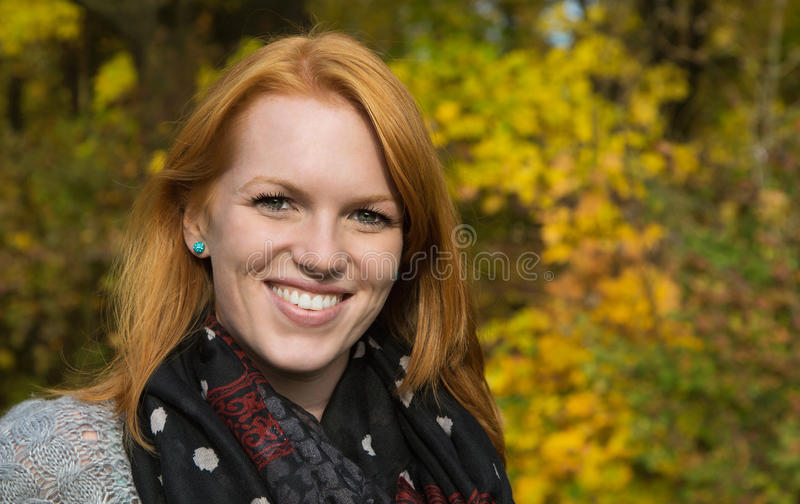 Natural red-haired young smiling woman in autumn on a walk. royalty free stock image