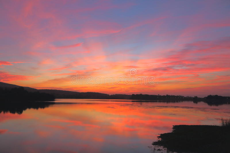 Natural redness colors in sky. Beautiful redness colors in blue sky feeling like painted with a brush. providing shining beauty falling shadow into the water of royalty free stock photo