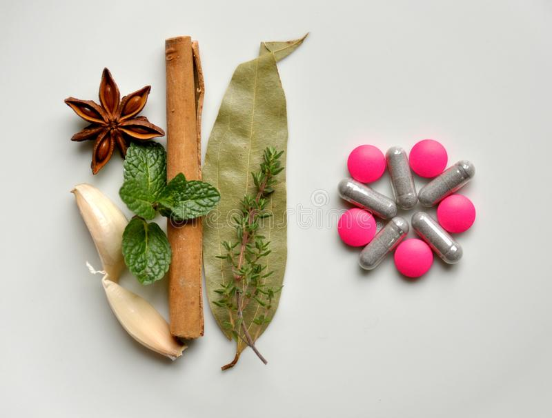 Natural remedy versus modern pills. Natural remedy versus modern medicine : various leaves with pills. Mint leaf, cinammon, thyme, anice star, garlic versus pink royalty free stock photography