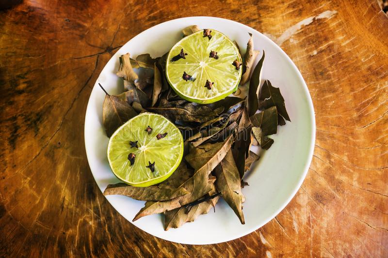 Natural repellent plate with lime, cloves and laurel on wooden table royalty free stock photo