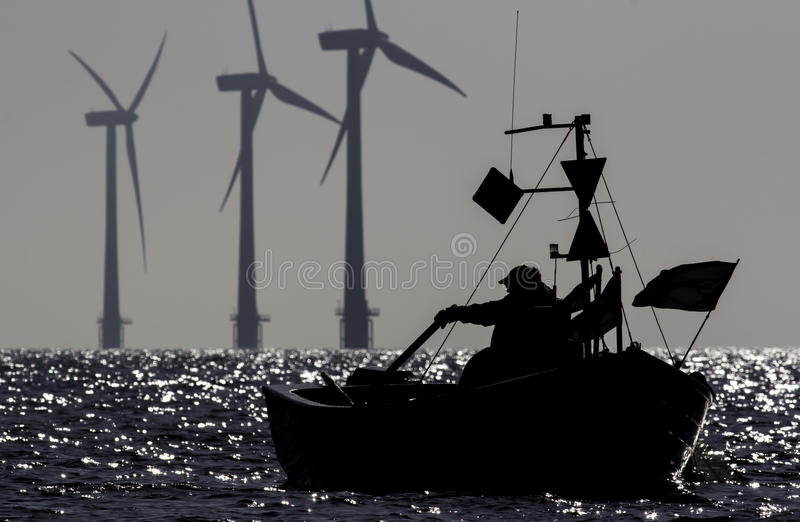 Natural resources. A lone fisherman drifts in the sea before dawn. In the background there is an offshore wind farm. The picture has numerous connotations royalty free stock photography