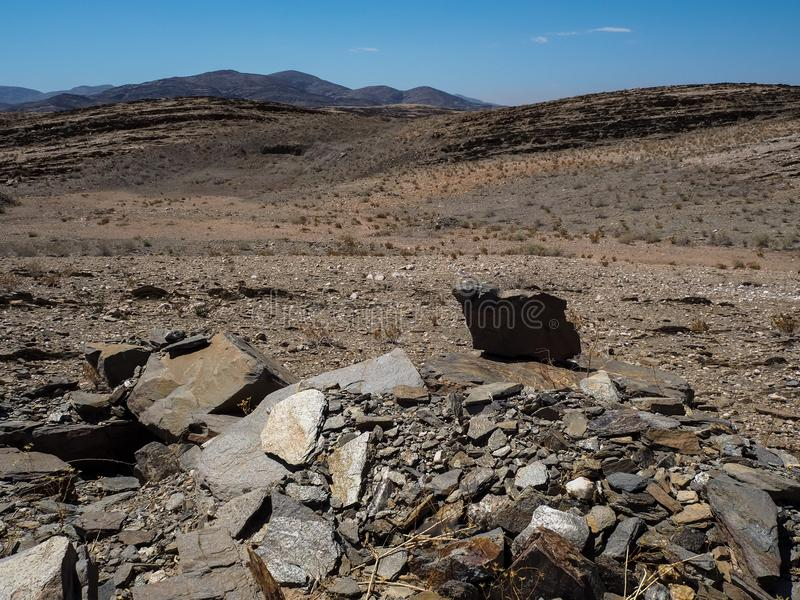 Natural rock mountain dried dusty landscape ground of Namib desert with splitting shale pieces, other stone and desert plant. Namibia stock images
