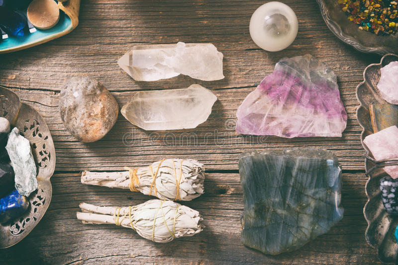 Natural rocks and white sage. Natural gemstones, white sage and incense on wooden board stock photo
