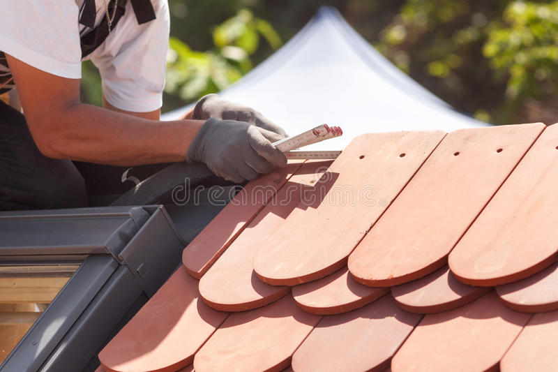 Natural roof tile instaalation. Roofer builder worker use ruller to measure the distance between the tiles. royalty free stock images