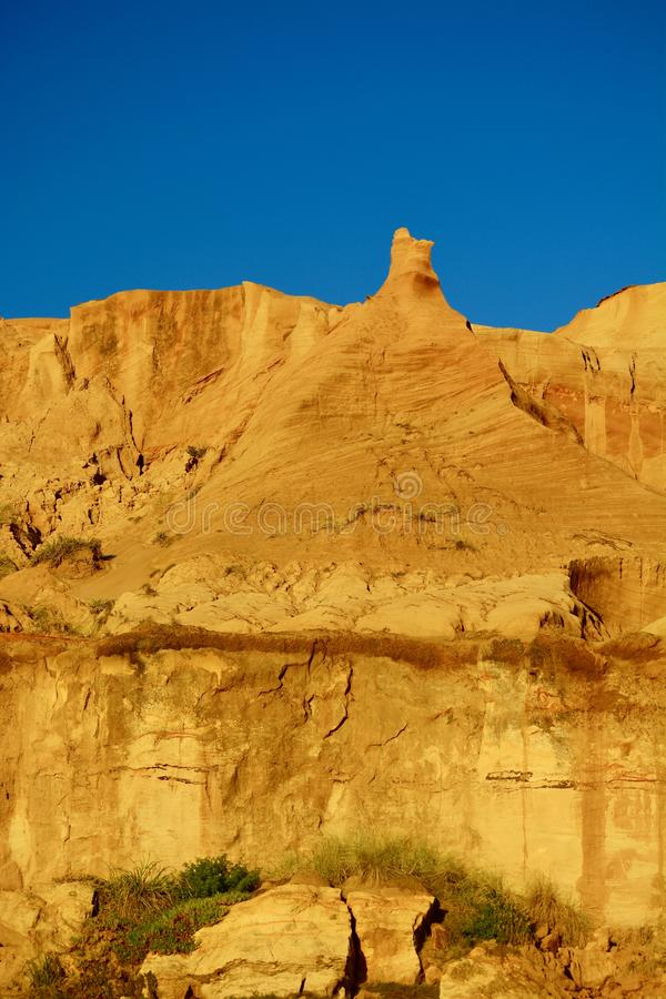 Natural sandstone formations: formed from cemented sand grains, yellow-orange in colour, forming rough cliffs against bright blue. Sandstone is a clastic royalty free stock images