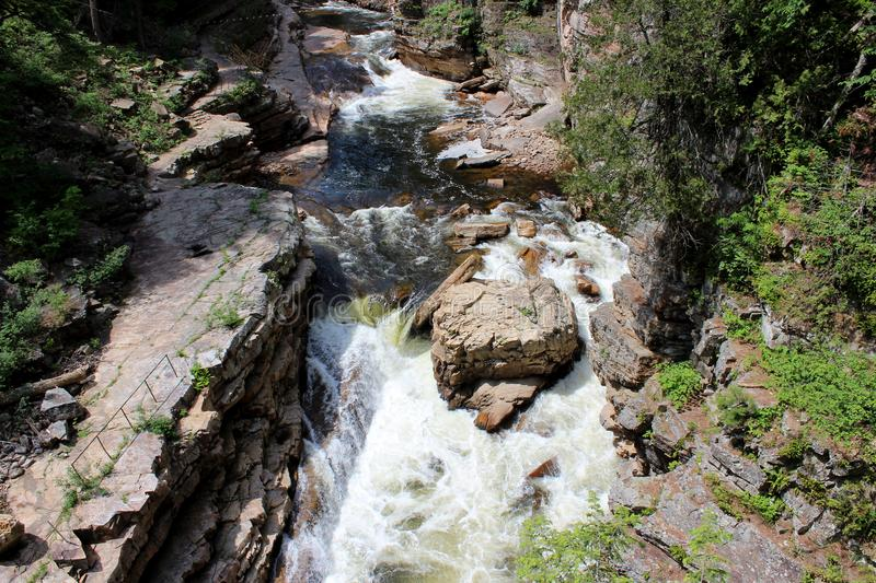 Natural scene with rushing water over rocky ledge, trees and other shrubs on either side. Sunny day with natural scene of rushing water over craggy cliffs, trees stock photo