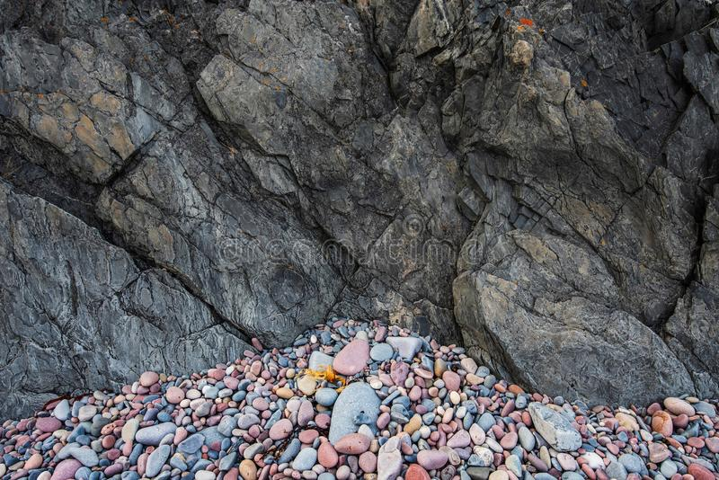 Natural seashore pebbles and dark slate rock stock images