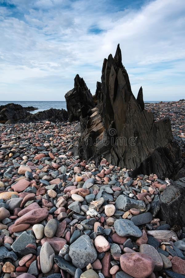 Natural seashore pebbles and dark slate rock stock photo