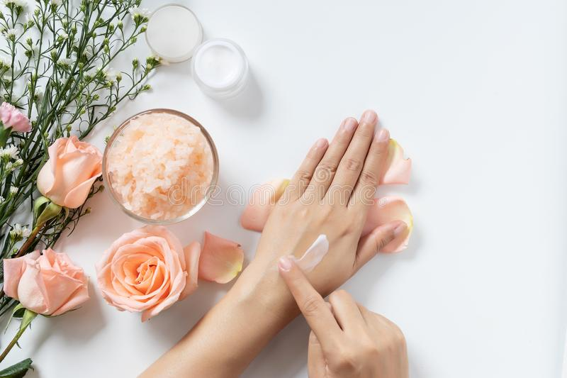 Natural skincare concept. woman apply white cream on her hands on white background with jar of cosmetic cream, salt spa scrub royalty free stock photos