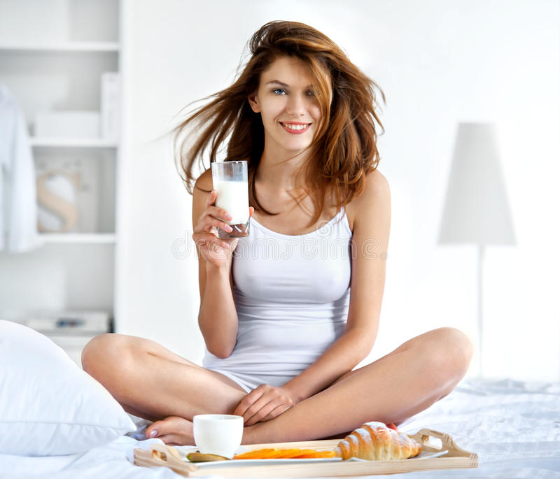 Natural smiling brunette holding glass of milk in bright bedroom stock photos