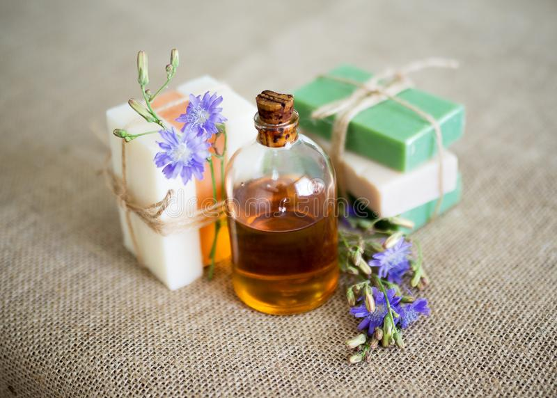 Natural soap and a bottle of aroma oil on jute background. Set of organic cosmetic products, selective focus stock image