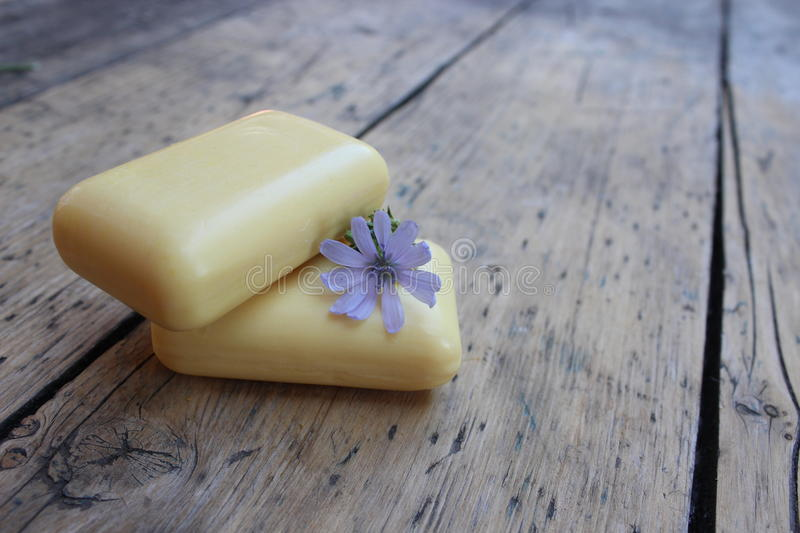 Natural soap and flower chicory. Natural soap with flower chicory on background of burlap royalty free stock image