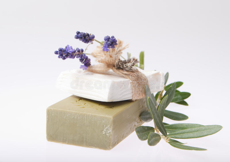 Natural Soaps. Composition with natural white and olive soaps lavender flowers and olive branch royalty free stock photos