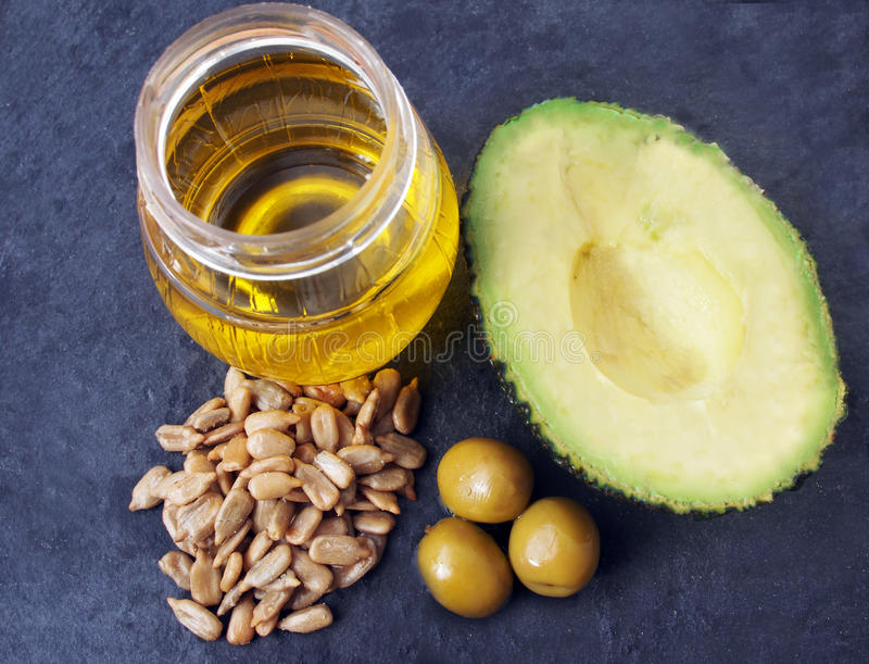 Natural source of vitamin E - sunflower seeds, olives, avocado, vegetable oil stock photography