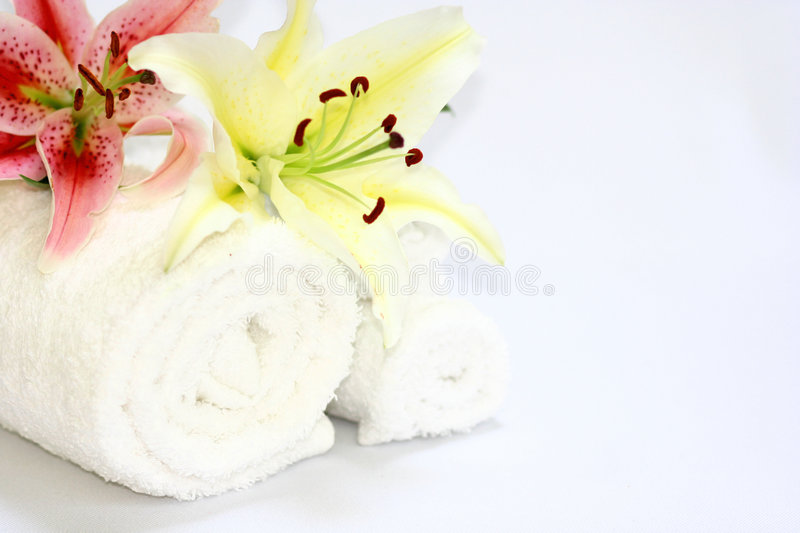 Natural spa. Spa setting with white towels and a lily, on white with copy space royalty free stock photo