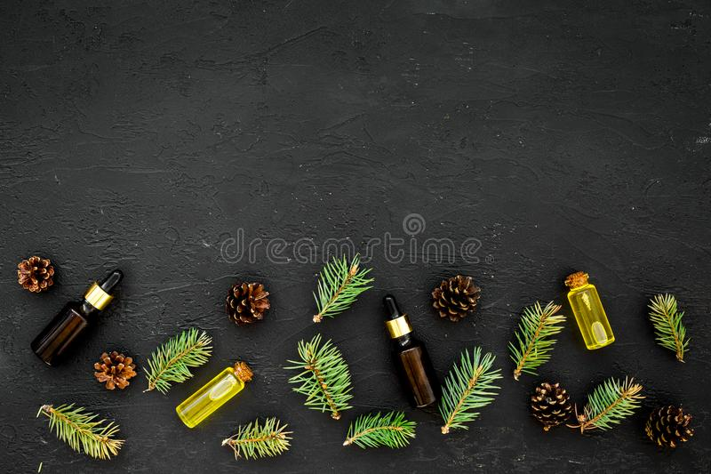 Natural spa cosmetics with pine essential oil for aroma on black background top view mock-up royalty free stock photos