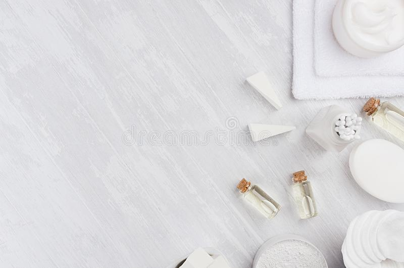 Natural spa massage oil and white cosmetics products, bath accessories with cotton towel on white wood board, top view, border. Natural spa massage oil and stock photography