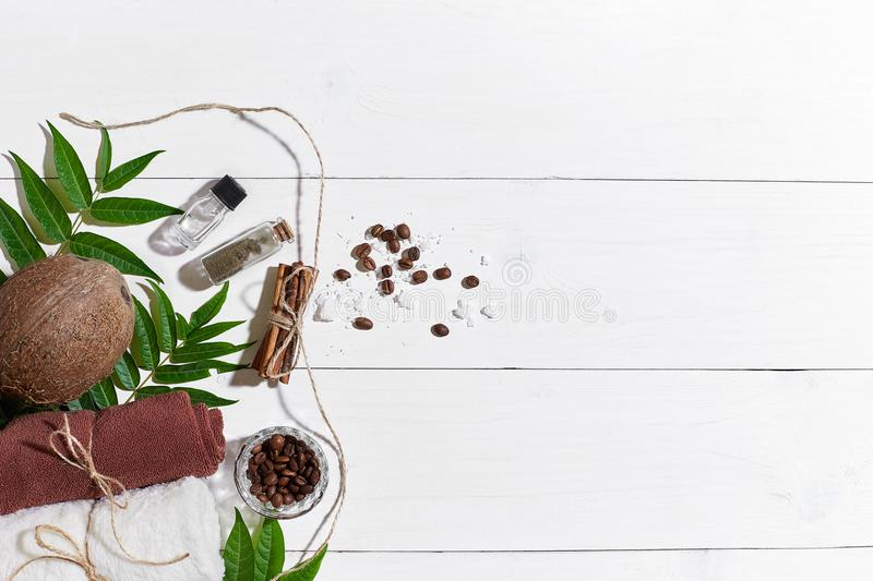 Natural spa set with coffee beans, cinnamon, sea salt, oil, brown towel, coconut and green leaves on white wooden royalty free stock photos
