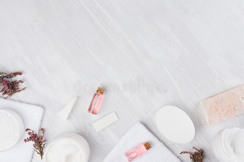 Natural spa white and pink cosmetics products and bath accessories with pink flowers as frame on white wood board, top view. Natural spa white and pink royalty free stock photography