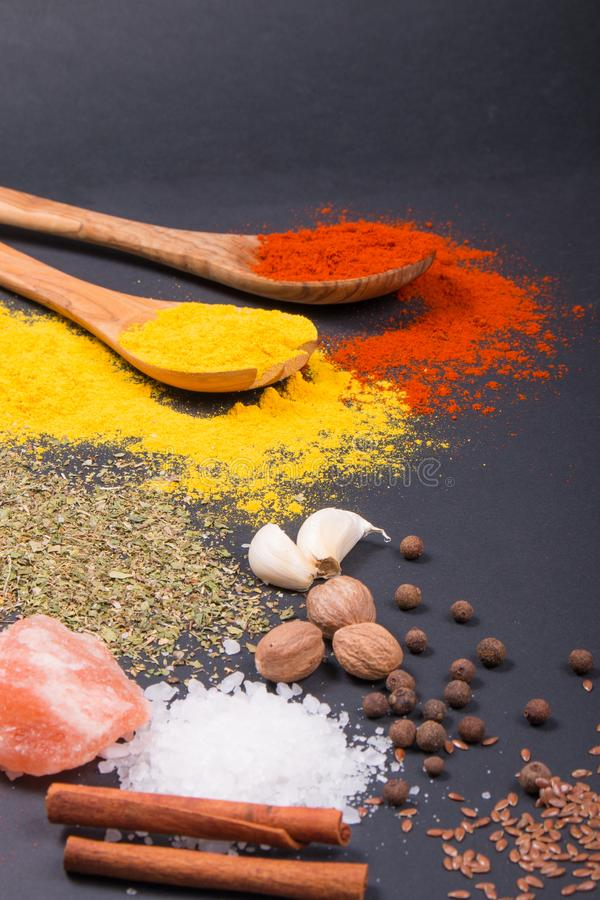 Natural spices and herbs scattered on dark background. Natural and bio ingredients for cooking. stock photo