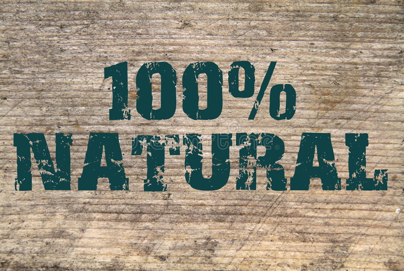 100% Natural stamped text on old plank. 100% Natural stamped green text on old plank- as background royalty free stock image
