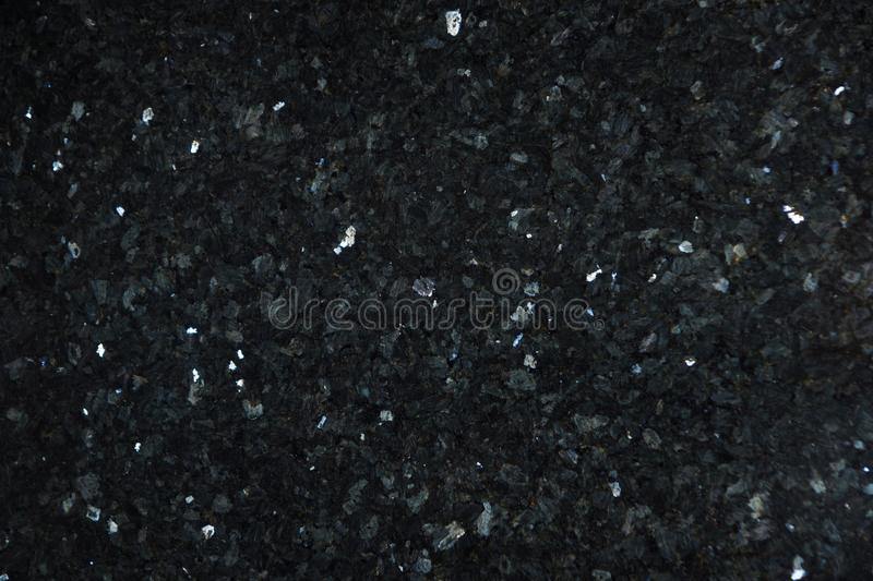 Natural stone of dark color with bright sparkles with bluish tint, called labradorite Emerald Pearl stock photo