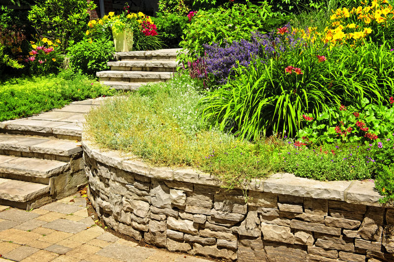 Natural stone landscaping. In home garden with stairs and retaining walls royalty free stock photography