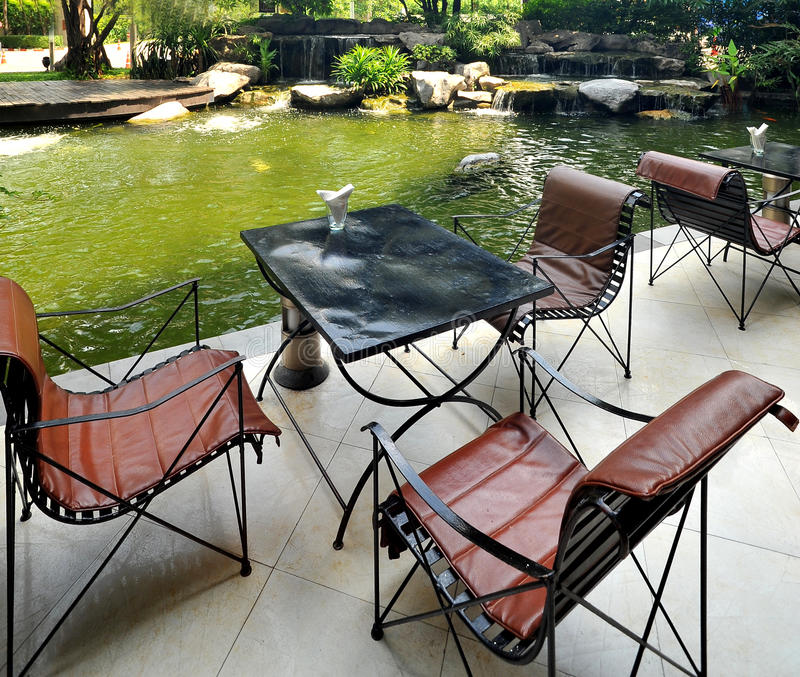 Natural stone pond and wooden chair stock photos