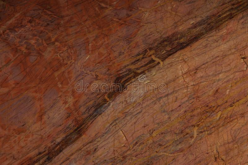 Natural stone of red color with yellow and claret veins.  royalty free stock image