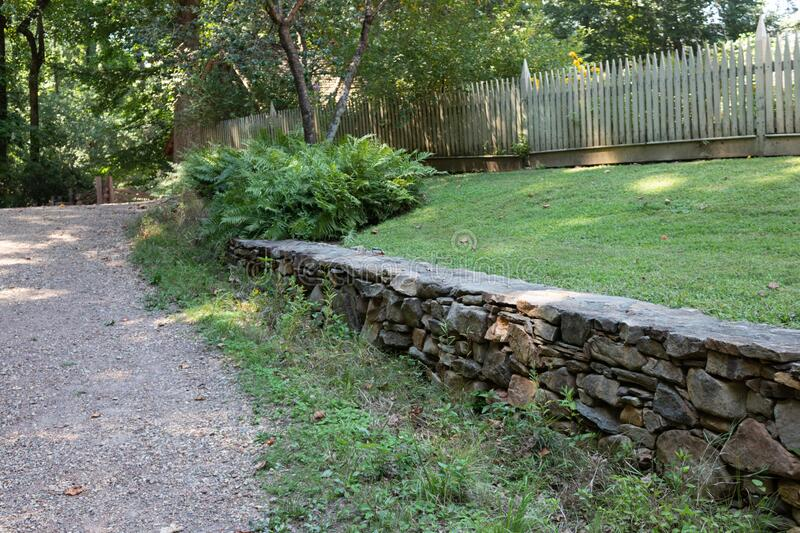 Natural stone retaining wall alongside a gravel path, green grass and tight picket fence. Horizontal aspect royalty free stock photography