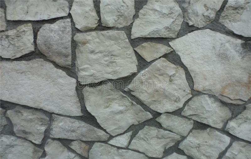 Natural Stone wall in Prato Italy. A close up of a wall made with large pieces of natural stone is made of mosaic in the city of Prato in Tuscany, Italy stock image