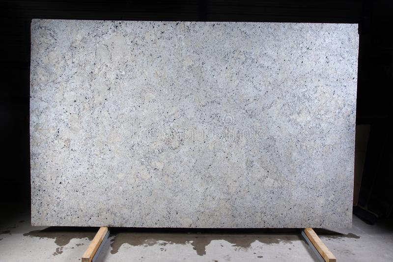 Natural stone of white color with dark specks, called granite Fantastic White stock images