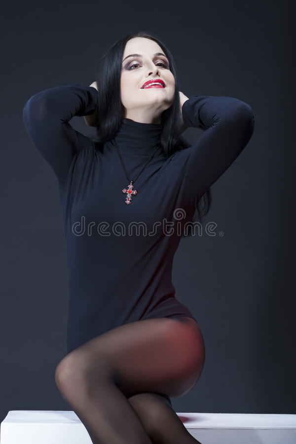Natural Studio Portrait of Smiling Sensual Caucasian Brunette Woman in Black Body Suit Posing on White Box Against Black royalty free stock photography