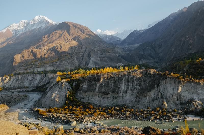 Colorful trees and river against mountain range in autumn. Natural sunlight shining at colorful trees and river against snow capped mountain peaks in Karakoram royalty free stock image