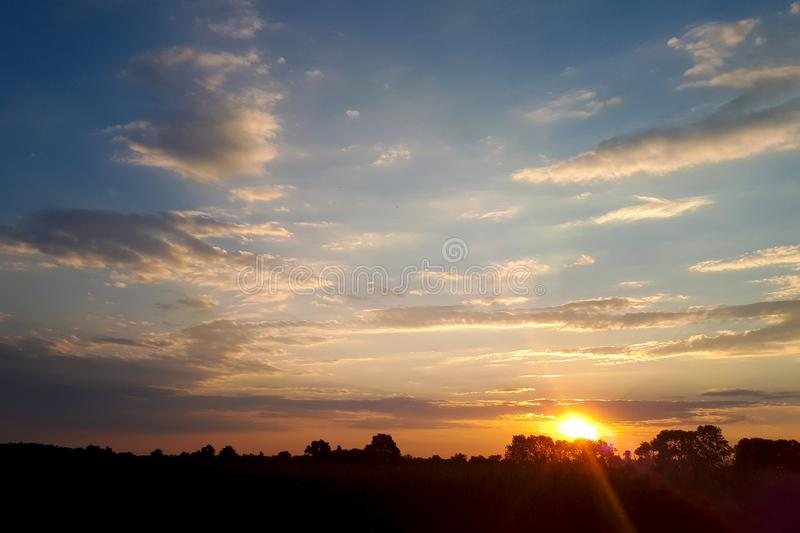 Natural sunset sunrise over field or meadow. Bright dramatic sky and dark ground. countryside landscape under scenic colorful sky. At Sunset Dawn Sunrise. Sun royalty free stock photos