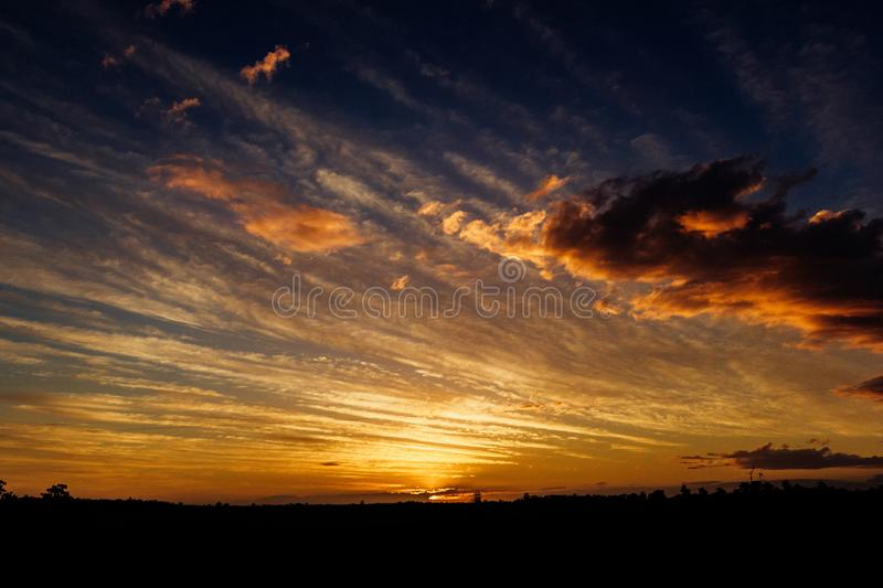 Natural Sunset Sunrise Over Field Or Meadow. Bright Dramatic Sky And Dark Ground. Countryside Landscape Under Scenic Colorful Sky stock images