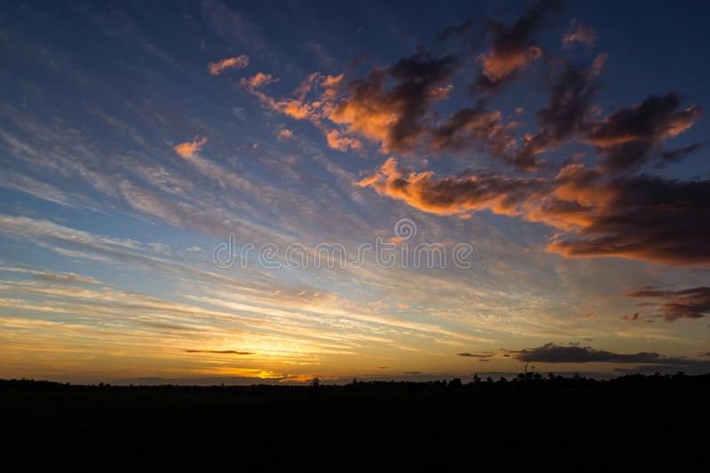 Natural Sunset Sunrise Over Field Or Meadow. Bright Dramatic Sky And Dark Ground. Countryside Landscape Under Scenic Colorful Sky. At Sunset Dawn Sunrise. Sun royalty free stock images