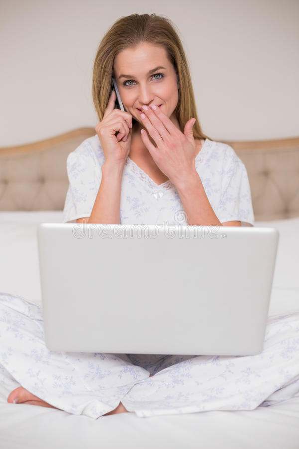 Natural surprised woman using laptop and phoning stock images