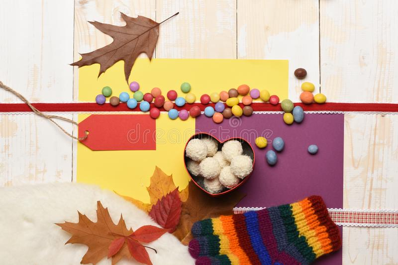 Natural sweets, paper tag or blank price list. Autumn mood concept. Sweets on colorful background, copy space. Box with coconut balls, autumn leaves, striped stock photo
