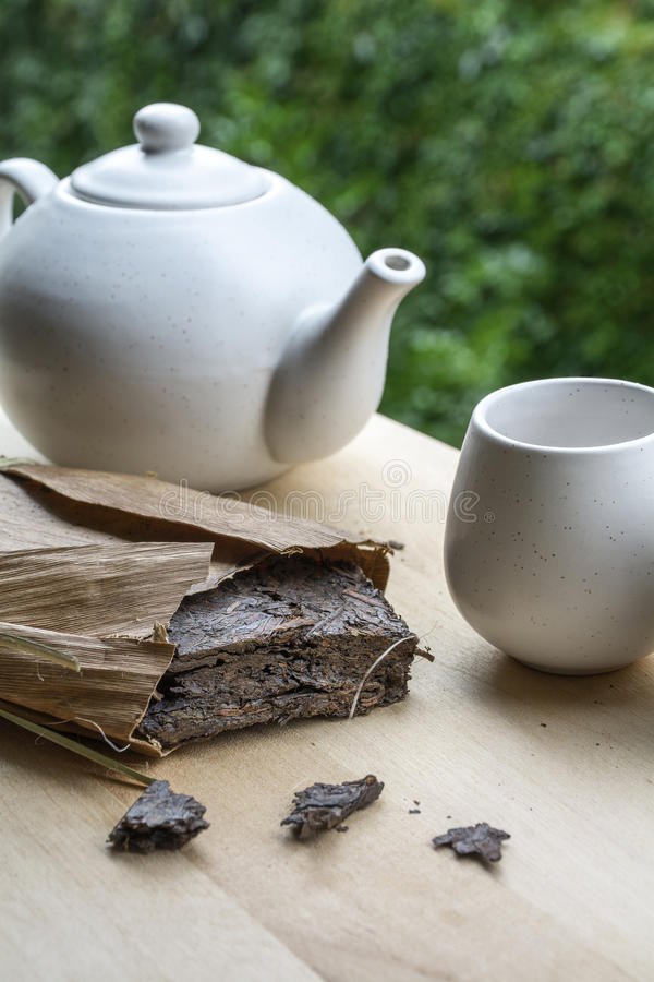 Natural tea with white teakettle and cup on the wooden table. And green leaves as background stock image
