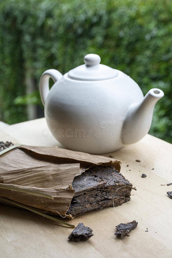 Natural tea with white teakettle on the wooden table. And green leaves as background stock photo