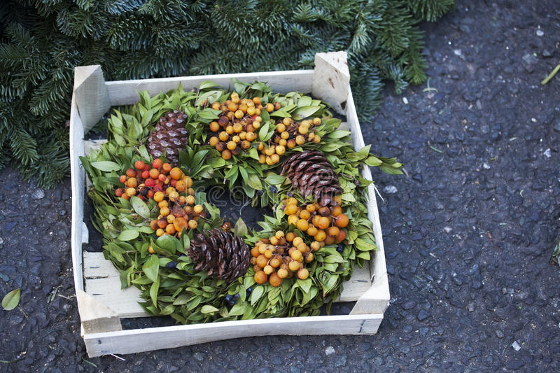 Natural twig wreath is decorated with pine cones, red berries, gold shells and a raffia bow. A natural twig wreath is decorated with pine cones, red berries royalty free stock photos