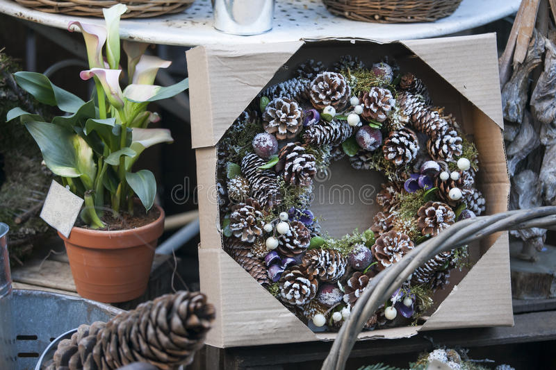 Natural twig wreath is decorated with pine cones, red berries, gold shells and a raffia bow. A natural twig wreath is decorated with pine cones, red berries royalty free stock images