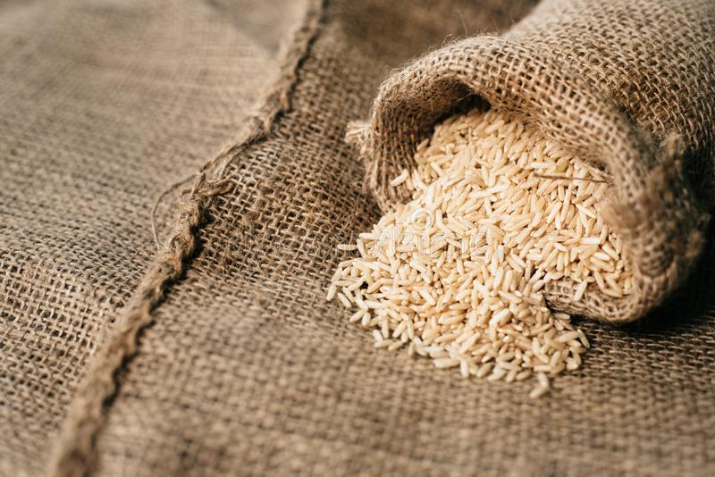 Natural unpolished brown rice on sack. healthy eating and food concept royalty free stock photos